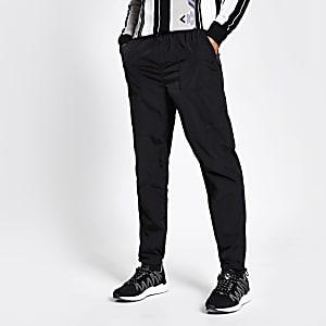 Schwarze Jogginghosen aus Nylon mit reflektierenden Streifen auf der Seite
