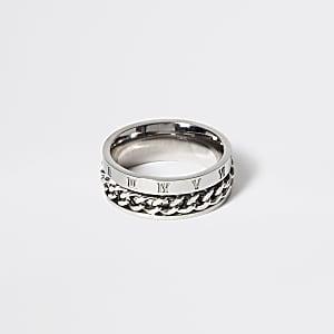 Zilverkleurige gegraveerde ring omringd door ketting