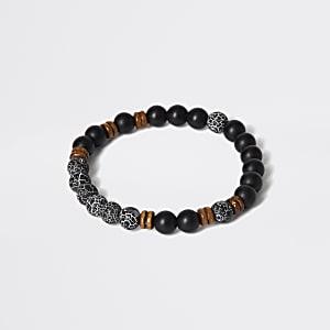 Armrreif mit schwarzem Stein und perlenbesetztem Holz