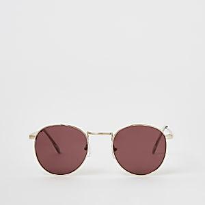 Goldene, runde Sonnenbrille mit rot getönten Gläsern