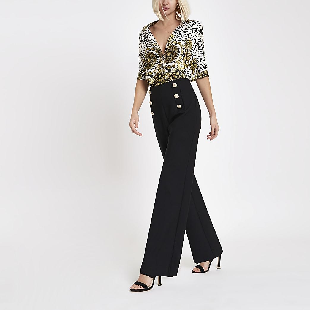 Schwarze Hose mit weitem Beinschnitt und goldenen Knöpfen