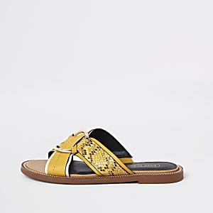 Gele platte sandalen met gekruiste bandjes en ring