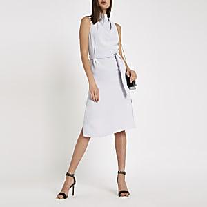 Blauwe mouwloze jurk met losvallende col en strikceintuur