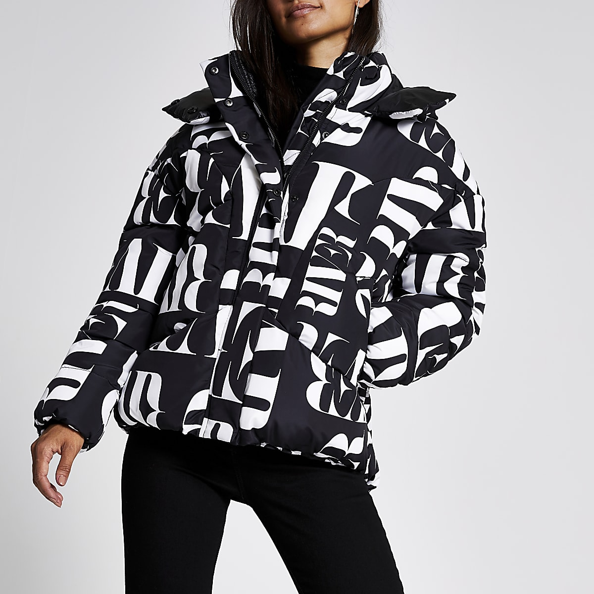 RI Petite - Zwarte gewatteerde jas met RI-print