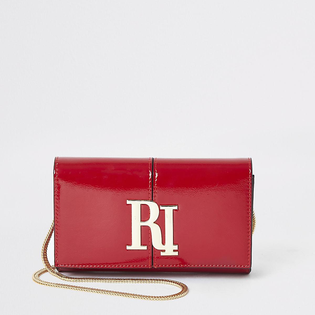 Rode lakleren onderarmclutch met RI-logo