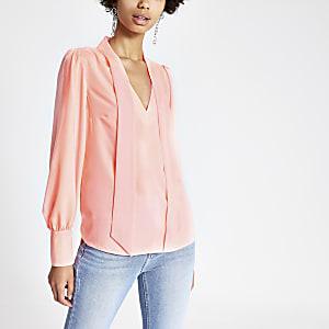 Koraalrode blouse met strik bij de hals