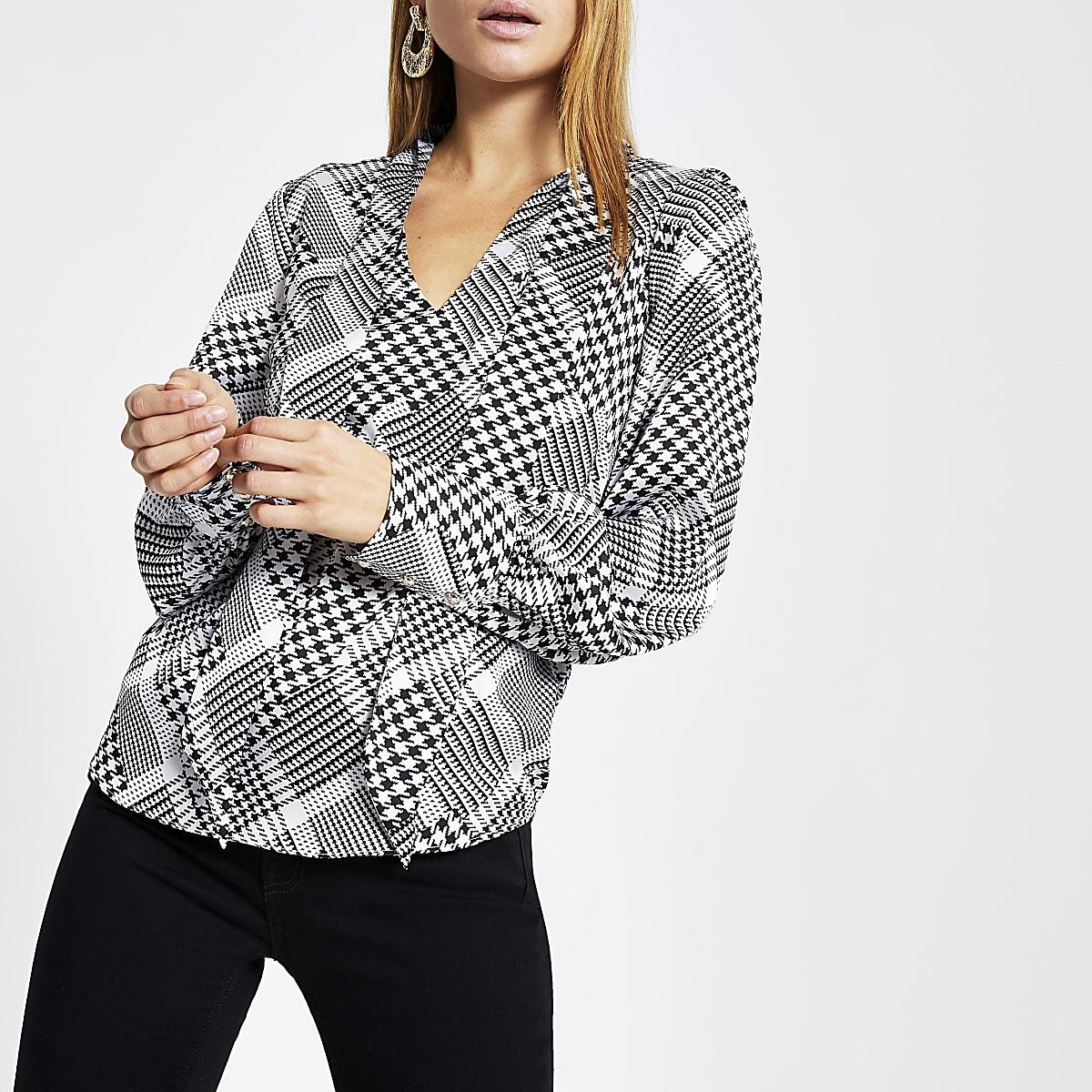 Zwarte blouse met pied-de-poule-motief en strik bij de hals