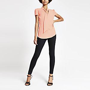 Koraalrode blouse met strik bij de hals en korte mouwen