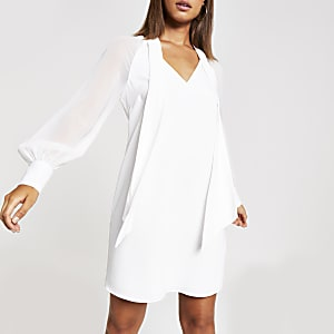 Mini-robe fluide en mousseline blanche nouée à l'encolure