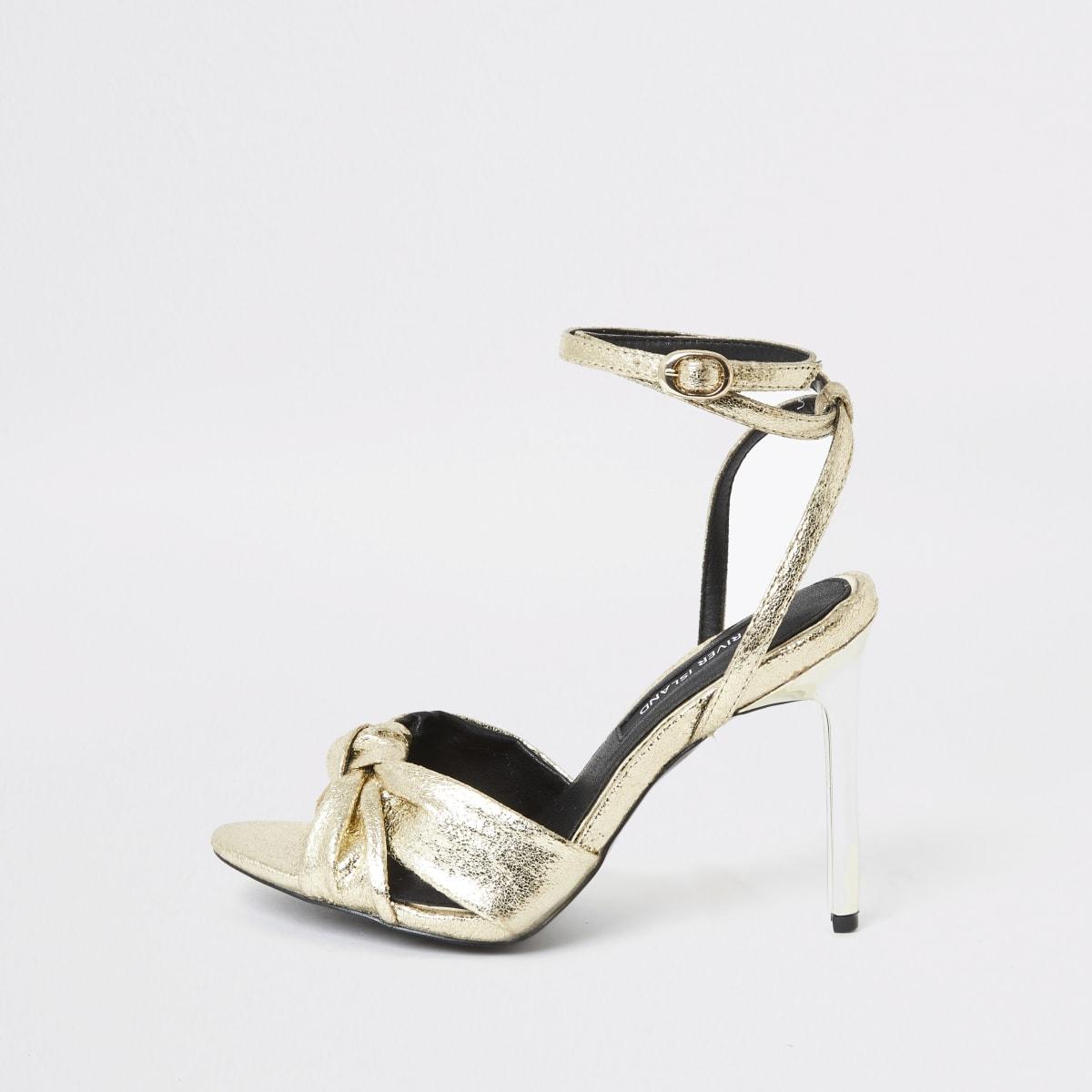 Goudkleurige sandalen met hakken en knoop aan de voorkant
