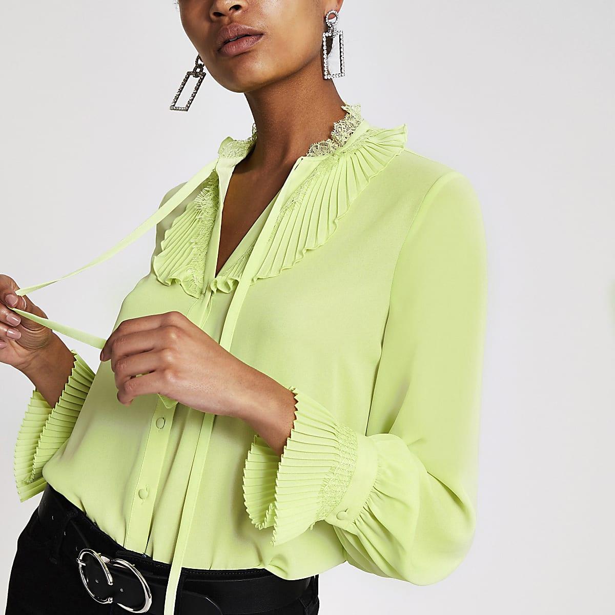Limoengroene blouse met kanten en strik bij de hals