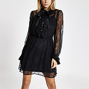Mini-robe trapèze noire en dentelle nouéeà l'encolure