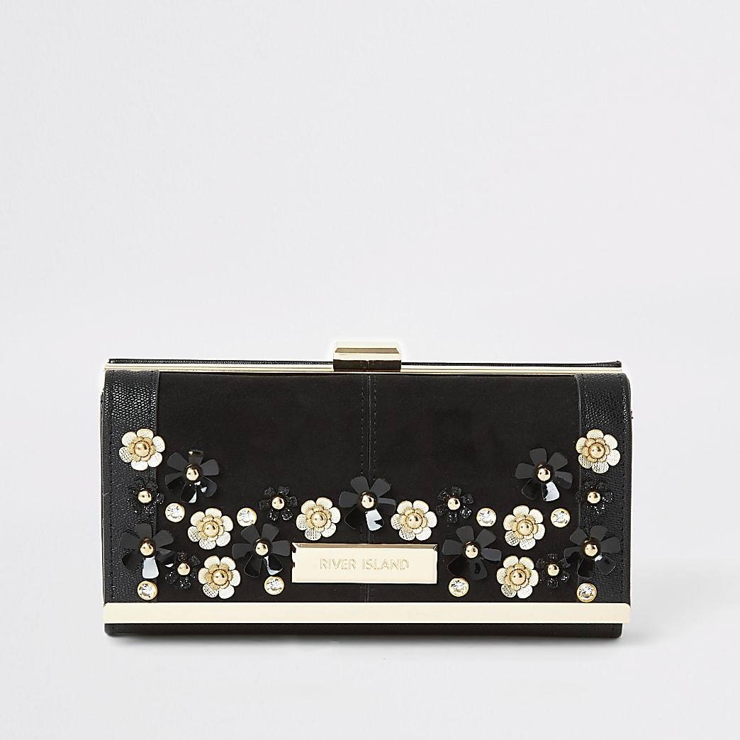 Schwarze Geldbörse mit Clipverschluss oben und Blumenverzierung