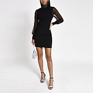 Zwarte hoogsluitende bodycon jurk met doorschijnende mouwen