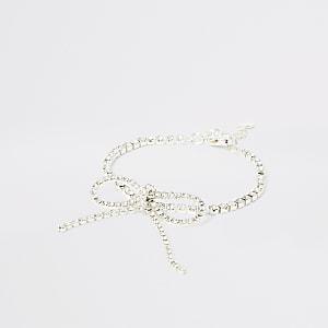Zilverkleurige armband met helderen siersteentjes en strik