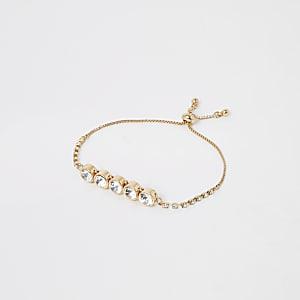 Goudkleurige armband met siersteentjes en juwelen