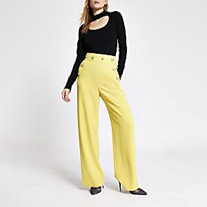 Gelbe Hosen mit weitem Beinschnitt und Knöpfen vorne