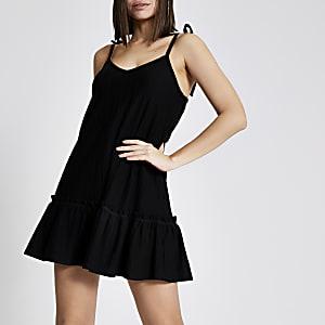 Schwarzes Minikleid mit Schößchen und Schulterträgern zum Binden