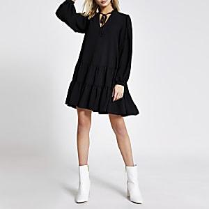 Zwarte gesmokte mini-jurk met lange mouwen en strik bij de hals