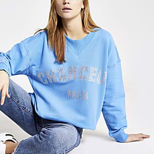 Blauwe sweater met 'Chanceux'-siersteentjesprint