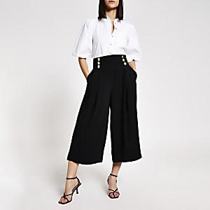Schwarze, kurze Hose mit weitem Beinschnitt und vorderem Knopf