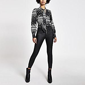 Zwarte blouse met pied-de-poule-ruiten en strik rond V-hals