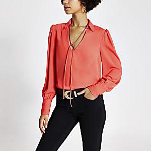 Koraalkleurige blouse met strik bij de hals en lange mouwen