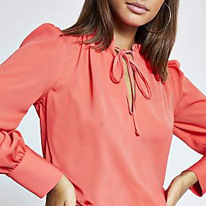 Koraalkleurige blouse met ruches, strik bij de hals en lange mouwen