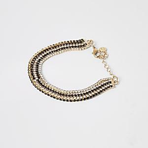 Goudkleurige gelaagde armband met siersteentjes