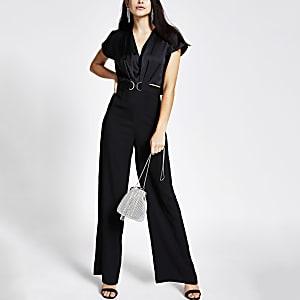 Zwarte jumpsuit met capemouwen en trens voor