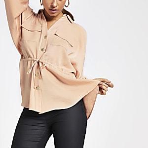 Chemise roseà manches longues nouéeà la taille