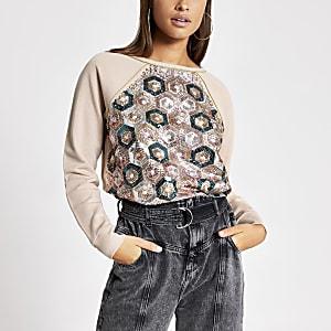 Roze ruimvallende sweater verfraaid met siersteentjes