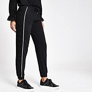 Pantalons de jogging amples noirs avec broderie anglaise sur lecôté
