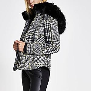 Schwarzer, eng geschnittener Mantel mit Muster und Kunstfellkapuze