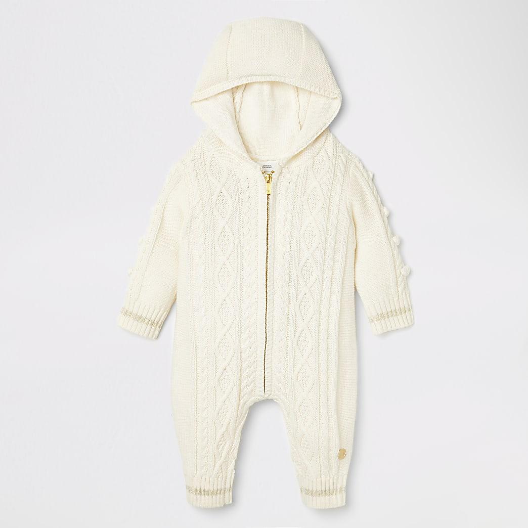 Crèmekleurig gebreid rompertje met pompons voor baby's
