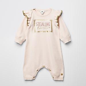 Roze gebreid rompertje met 'Stealing hearts'-tekst voor baby's