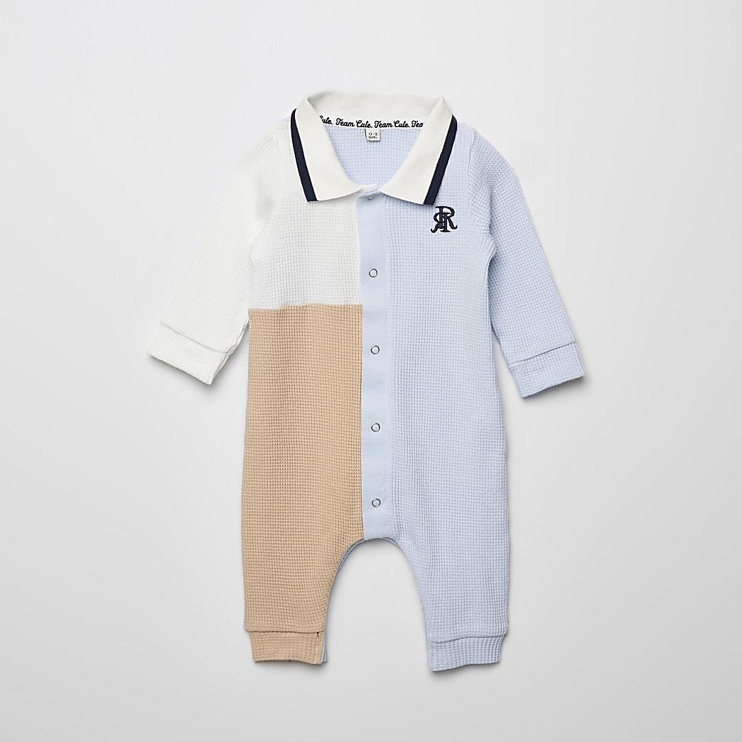 Blauwe polo baby-growrompermet kleurvlakken en wafeldessin voor baby's