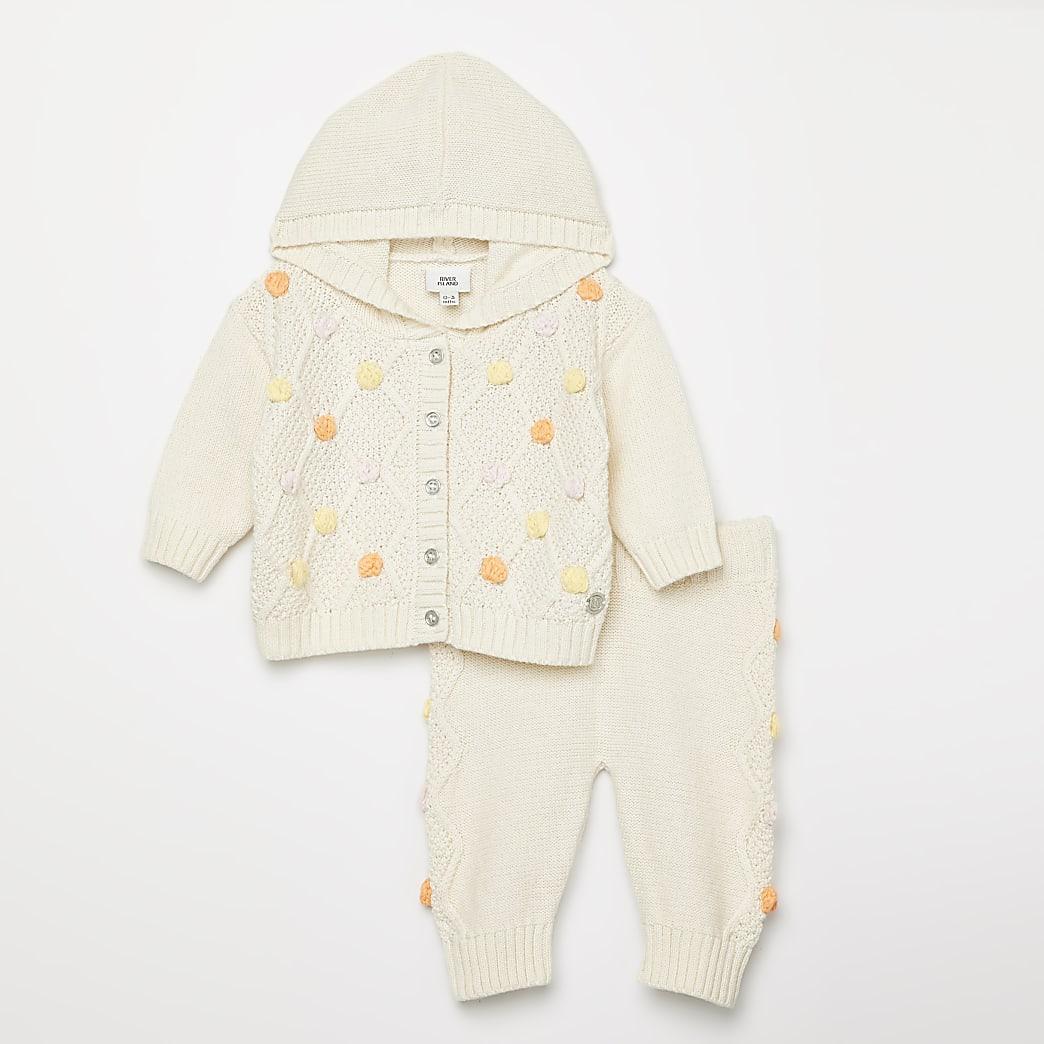 Crèmekleurig gebreid vest outfit met pompons voor baby's