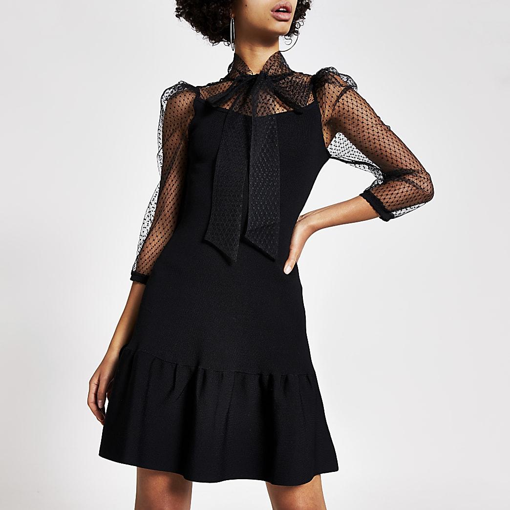 Schwarzes Kleid mit gepunktetem Netzstoff und Bindeschleife am Kragen