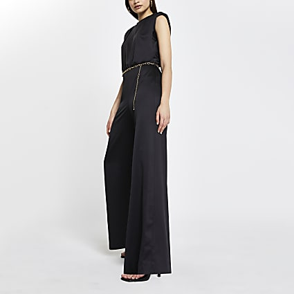 Black shoulder pad chain belted jumpsuit