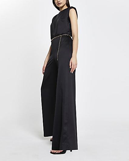 Black shoulder pad chain belted jumpsuit