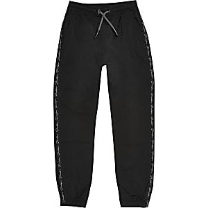 Zwarte nylon joggingbroek met bies voor jongens
