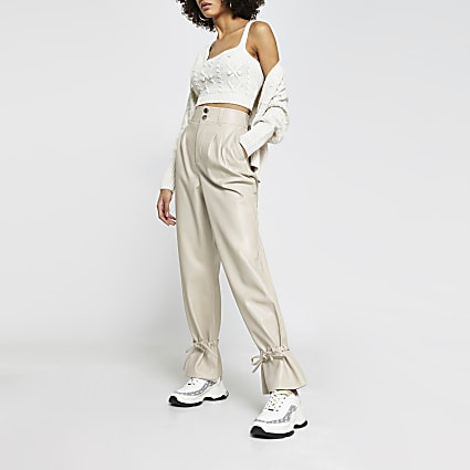 Cream faux leather tie bottom trousers