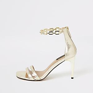 Goudkleurige sandalen met hak en wijde pasvorm en kettinkje bij de enkel