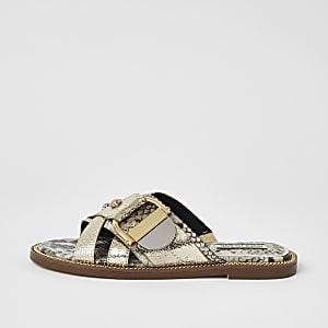 Goudkleurige platte sandalen met gekruiste bandjes en ring