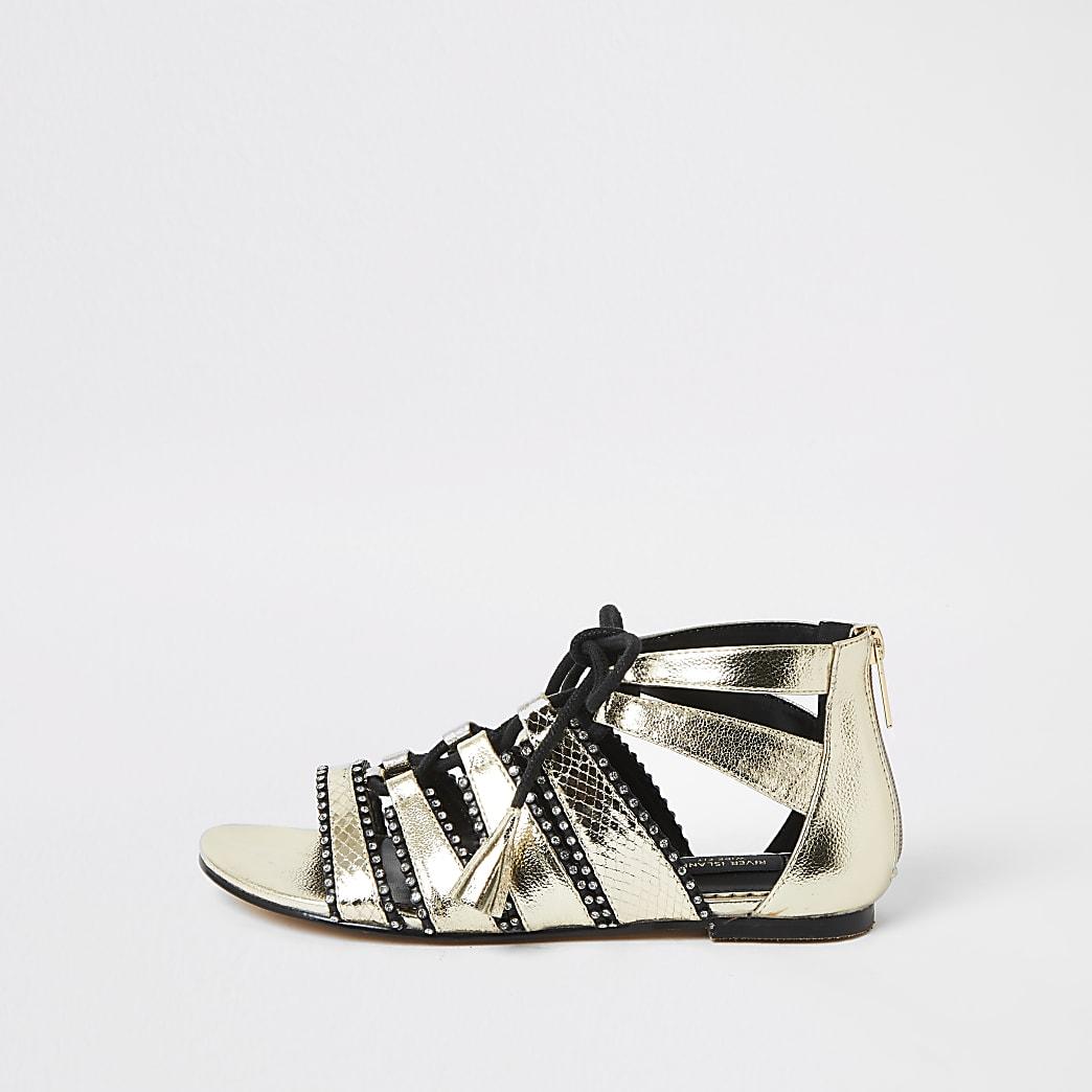 Goudkleurige sandalen met wijde pasvorm en vetersluiting en siersteentjes