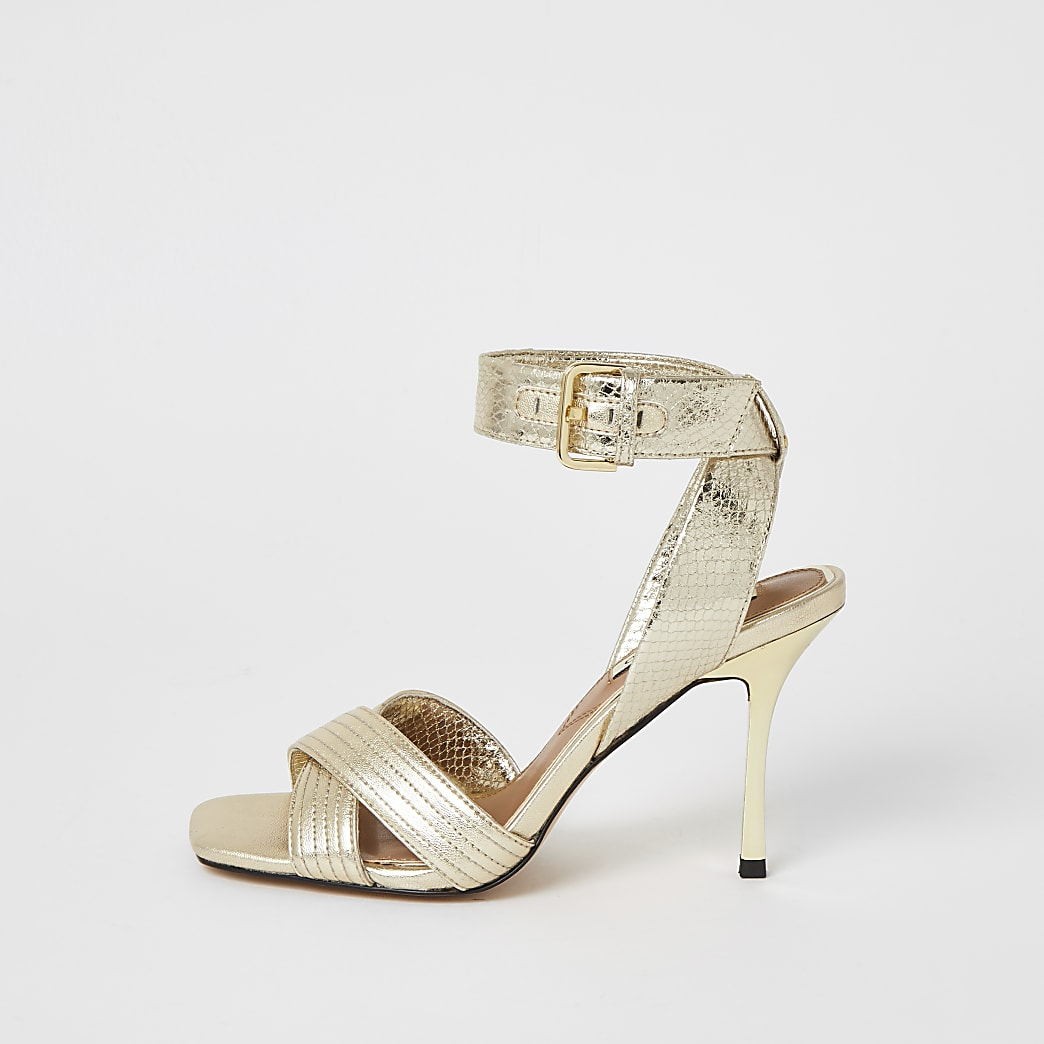 Goudkleurige metallic sandalen met gekruiste bandjes en hak