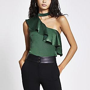 Groene top met choker hals en franje en een blote schouder