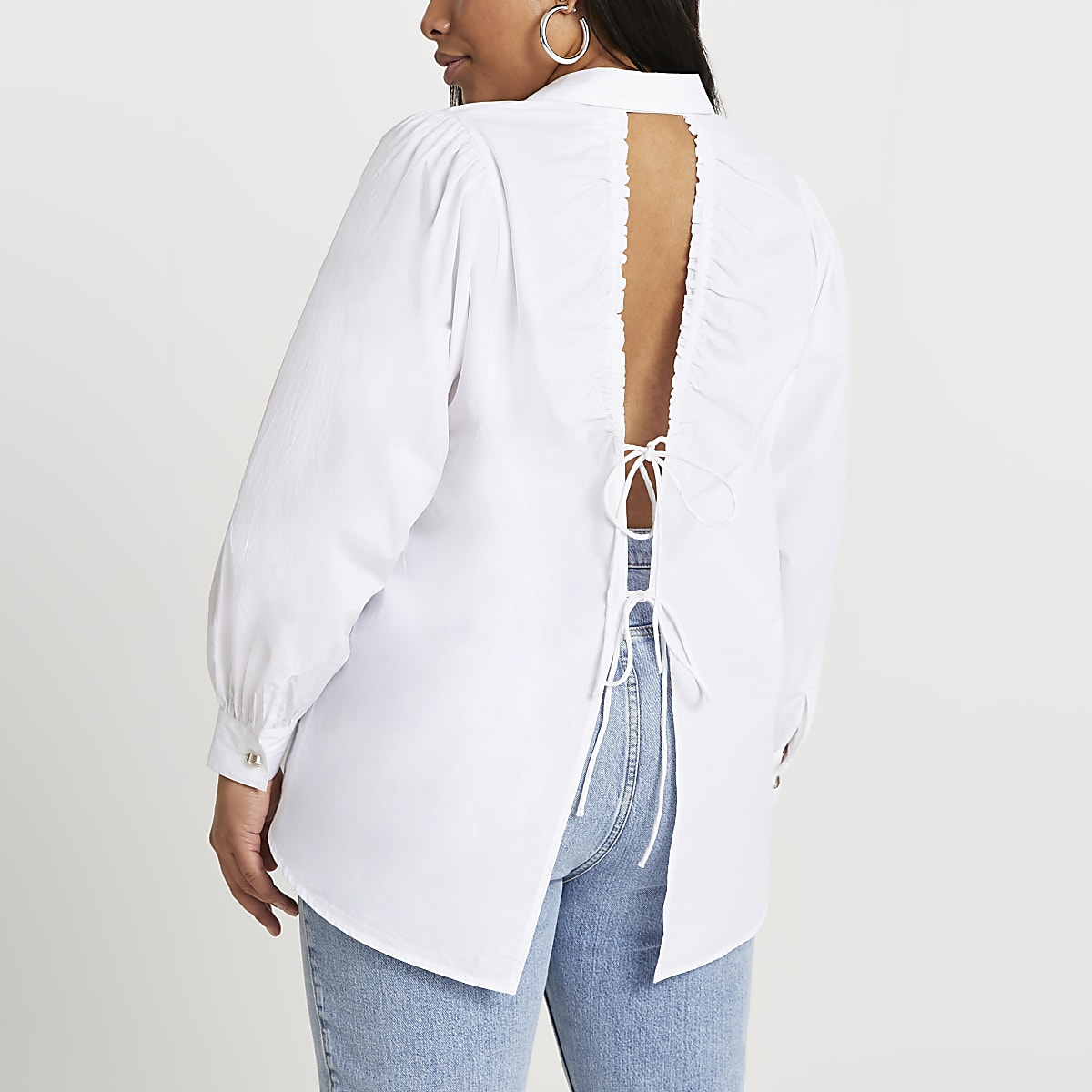 Woman wears white shirt with open back with ties, jeans and silver hoop earring.