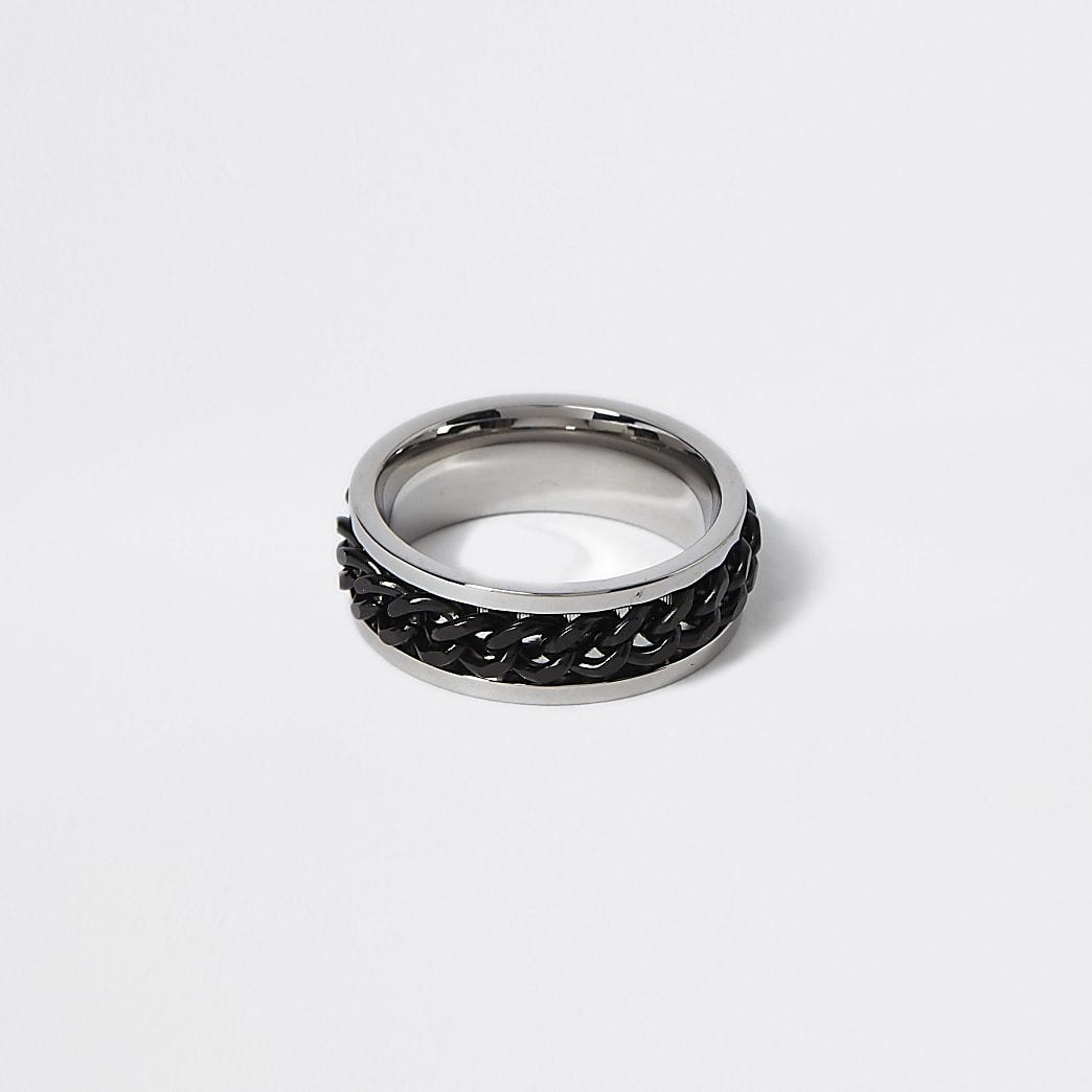 Zilverkleurige ring omringd door zwarte ketting met reliëf